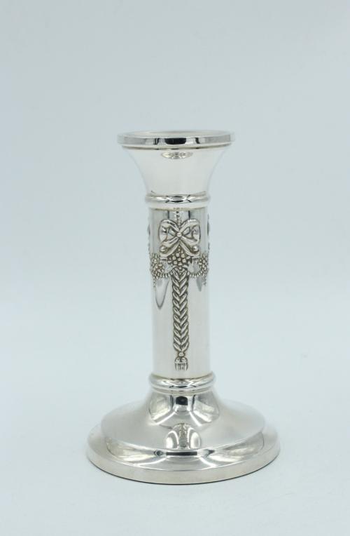 Een zilveren kandelaar met een guirlande op de schacht van de kandelaar.