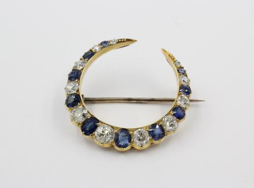 Gouden maanbroche met blauwe saffieren en briljanten