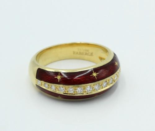 Een 18 kt geelgouden ring met over het midden een strip gezet met aflopende briljanten . De zijkanten zijn voorzien van rood emaille . Model nummer F2576. 0.22 ct aan briljant. Gemerkt en genummerd Fabergé 81/1000