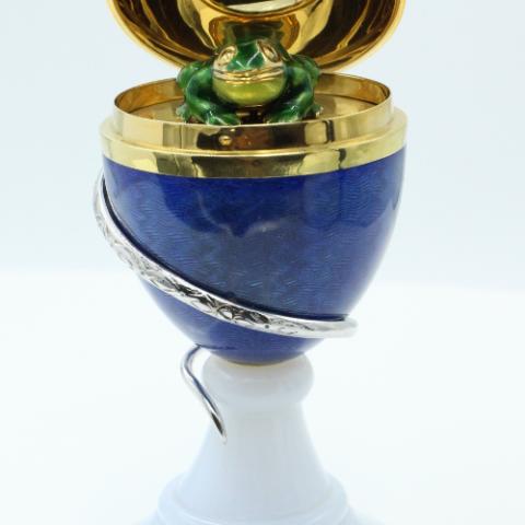 Een 18 kt gouden, geëmailleerd Fabergé ei, voorstelling van een kikker en een slang. Het gouden ei staat op een chalcedon voet. Tevens gezet met een briljant van 0.035 ct en een smaragd van 0.06 ct . Het object is gelimiteerd en genummerd 35/75