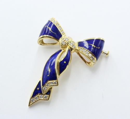 Strikbroche 18 kt met blauw emaille gemerkt Fabergé. Genummerd 15/500. 0.49 ct aan briljanten