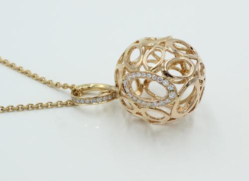 18 kt rosé gouden hanger, Een opengewerkte gouden bol , bezet met briljanten. 23 mm doorsnede