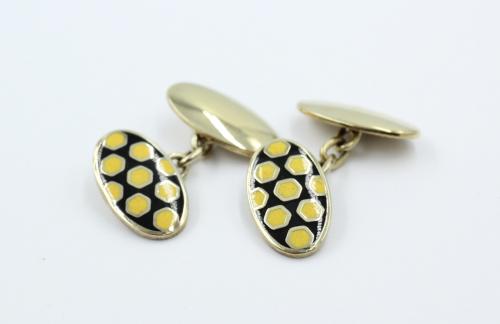 Zilver vergulde manchetknopen , Engels met kettingverbinding, De bovenplaat geemaillerd met zwart en geel.De achterplaat is geheel glad . Plaatdikte is 2 mm . De ovalen zijn groot 19½ bij 11½ mm. Bruto 13.78 gram