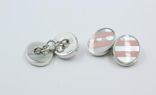 Een paar zilveren ovale knopen en jumelle met kettingverbinding. Engelse manchetknopen ,ovaal 17½ bij 13½ mm . dikte 2.5 mm. De kopen zijn aan de bovenzijde bewerkt met parelmoer en roze emaille. 10.8 gram