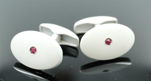 Een paar zilveren ovale knopen met een crème witte keramisch coating. Centraal een klein robijntje. Gewicht 11.31 gram . Ovaal grootte 20 bij 12½