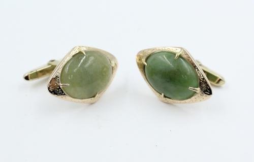Een paar ruitvormige manchetknopen vervaardigd van 14 kt goud en gezet met een cabochon oaal geslepen Grossulaar. Grossulaar behoort tot de Jade groep. De knopen zijn niet nieuw maar verkeren in prima staat. Mooi handwerk. Bruto 10.07 gram