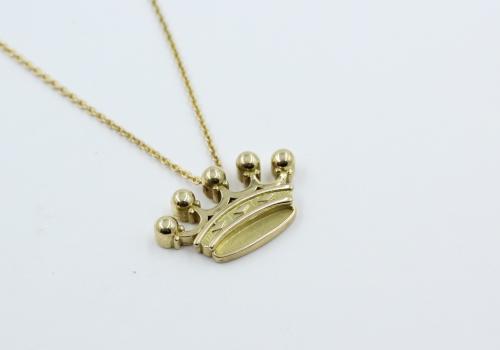 Een18 kt geelgouden ankercolliertje met jonkvrouw kroontje. De kroon met collier zijn uit eigen atelier . De breedte van de kroon is 23.5 mm mm. 4 mm dik