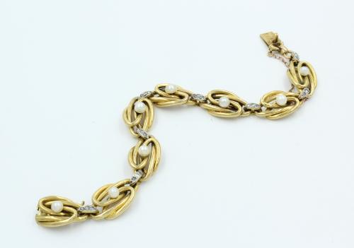Antiek gouden armband , 8 grote ovale knoop schakels, waarop een 4 mm oriëntparel gemonteerd, de tussenschakels met 3 diamantjes bewerkt. Breedte 12 mm . Gewicht 28.19 gram