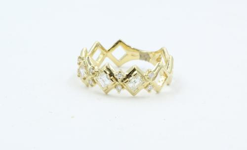 Een 18 karaats geelgouden rijring , waarin 3 carré geslepen diamanten vergezeld van 8 kleine diamantjes. 0.47 ct totaal . De ringmaat is 17.25. 6.8 mm breed