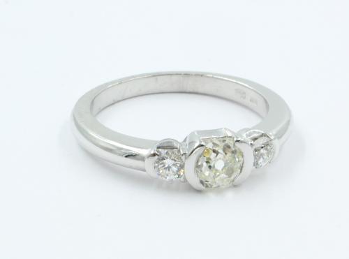 Een 14 karaats witgouden ring waarin centraal een bolsjewiek geslepen diamant van 0.68 ct, geflankeerd door twee briljanten Top wesselton VVS1 van elk 0.10 ct.