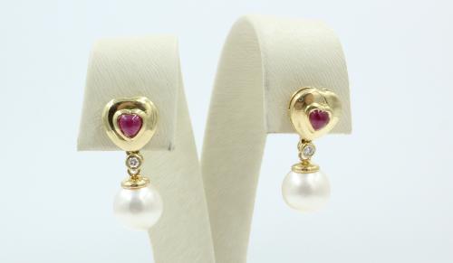Hartvormige oorbellen waarin een cabochon geslepen robijntje, daaronder een klein briljantje en daaronder een 7 mm grote Akoya parel . Vervaardigd uit 18 karaats geelgoud.
