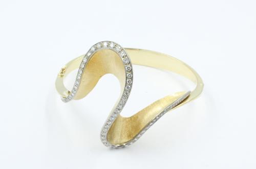 Een fraaie 18 karaats gouden armband, als een slinger over de pols, gezet met 65 briljanten. Een ontwerp uit de jaren 70. De band weegt 35.4 gram . Het geschat gewicht aan briljant is 1.50 ct