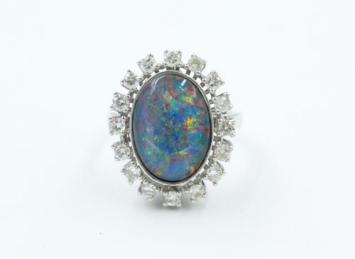 Een 14 karaats witgouden ring waarin een ovale opaal triplet ( onyx, opaal, en bergkristal) 15 bij 11 mm . Om de opaal 16 briljanten van elk 0.03 ct . Bruto 7.2 gram