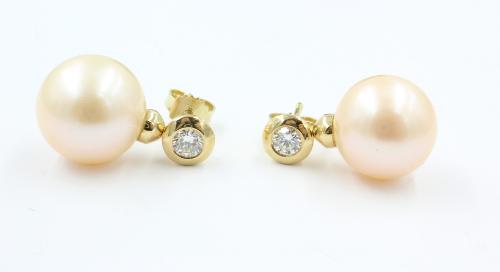 Een paar18 karaats gouden pareloorhangers met roze zoetwaterparels van 12 mm en elk een briljant van 0.25 ct
